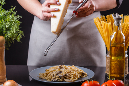young woman in a gray apron preparing pasta.