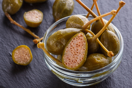 pickled capers on a dark stone background.