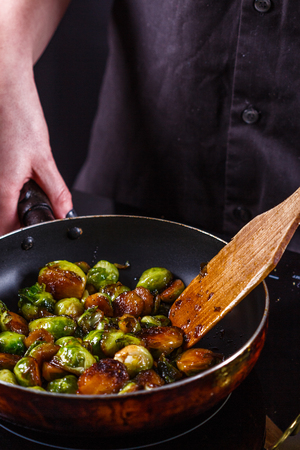 young woman fries Brussels sprouts on a frying pan. 版權商用圖片