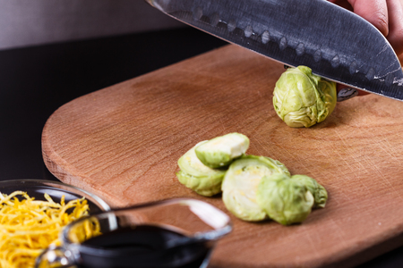 young woman cuts Brussels sprouts on a wooden cutting board.