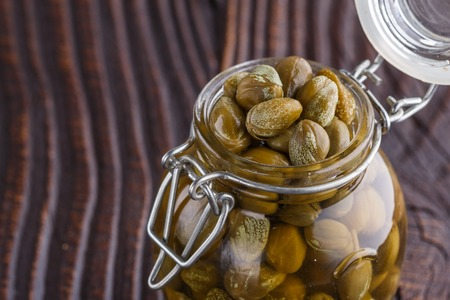 pickled capers on a wooden rustic background.