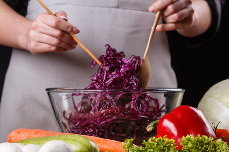 a young woman in a gray apron mixes a salad of red cabbage.