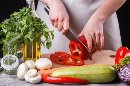 young woman slicing peppers in a gray apron. Imagens