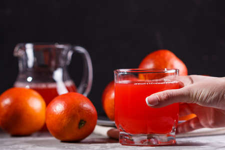 young woman in a gray apron takes a glass of juice blood orange.