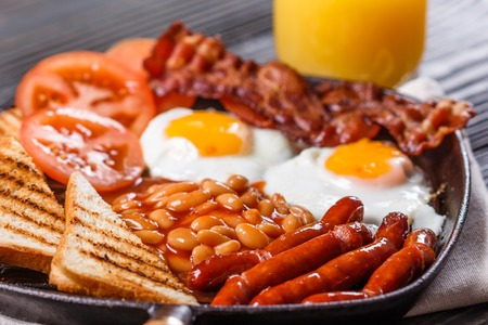 delicious English breakfast on a dark rustic background. Stock Photo