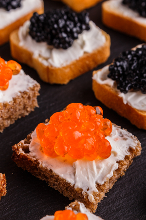 Snack with red and black caviar on a stone plate. 版權商用圖片