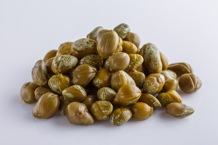 Pickled capers on a white acrylic background. Stock fotó