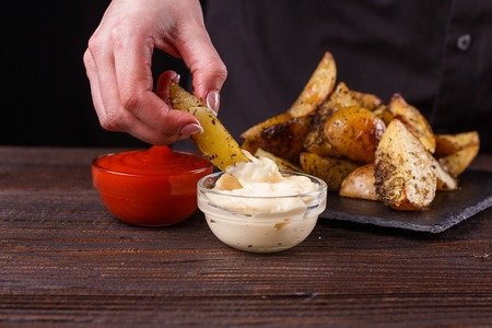 young woman dip fried potatoes to mayonnaise sauce.