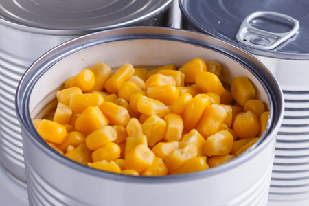 Canned corn in a iron can on white background. Stock fotó