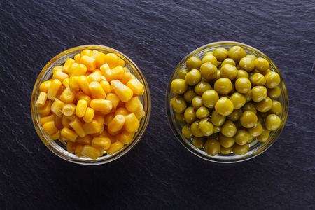 canned corn and green peas in a glass bowl on a dark stone background.