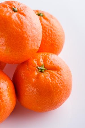 mandarina jugosa sobre un fondo de acrílico blanco.