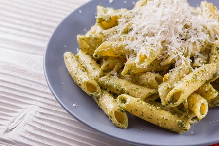 pasta pesto on a white wooden background.