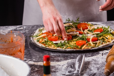 young woman in a gray aprong prepares a vegetarian pizza. Imagens