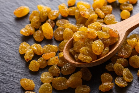golden raisins on a dark stone background.
