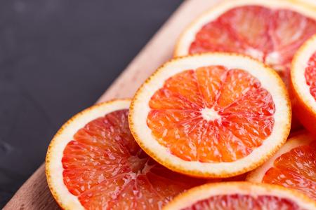 Blood orange cut in circles on a dark background. Stock Photo
