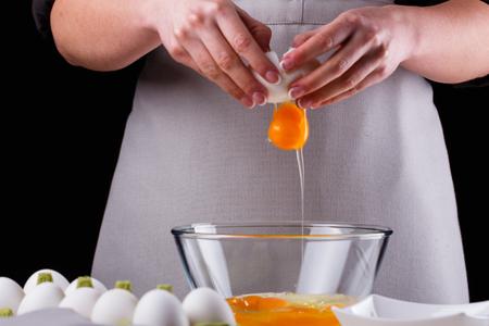 jeune femme dans un tablier gris casse les œufs.