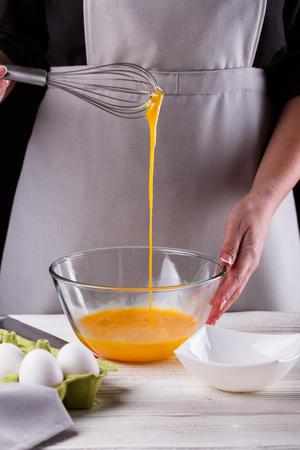 young woman in a gray aprons breaks the eggs.