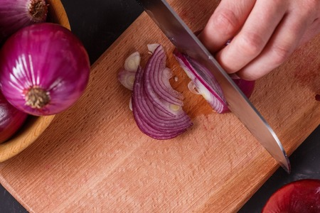 young woman in a gray aprons cuts red onion.