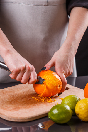 young woman in a gray aprons, cuts an orange zest