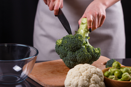 young woman in a gray aprons cuts cauliflower broccoli.