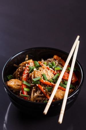 Buckwheat noodle in a black bowl on chicken fillet.