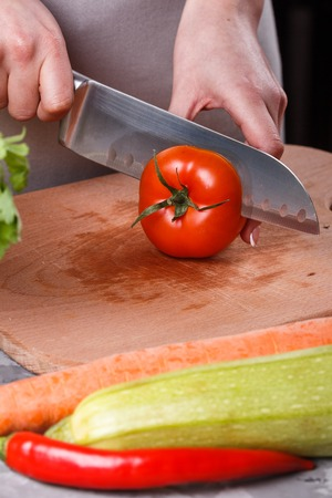 young woman slicing a tomato in a gray apron.