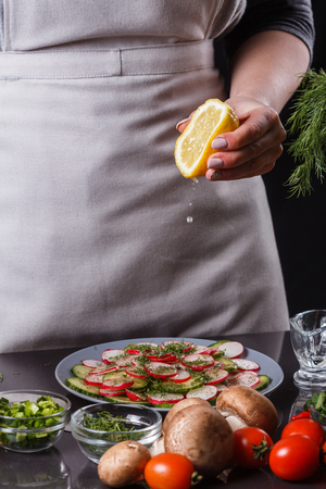 young woman in a gray apron is preparing a cucumber and radish salad. Фото со стока - 122576489
