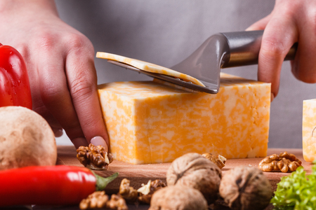 young woman slicing cheese