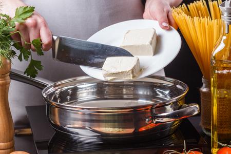 young woman  putting chopped butter on chopping board in frying pan.