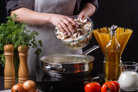 young woman adding mushrooms into frying pan Stock Photo