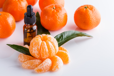 Peeled mandarin orange with essential oil bottle