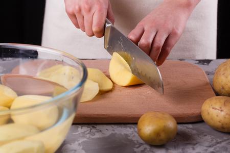 young woman cutting potatoes Banco de Imagens