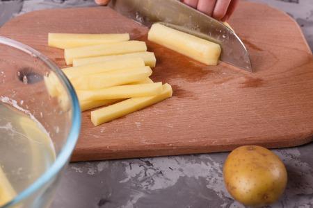 closeup of young woman cutting potatoes