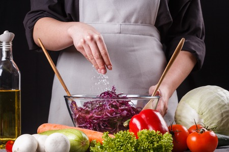 Young woman seasoning red cabbage salad in a glass bowl