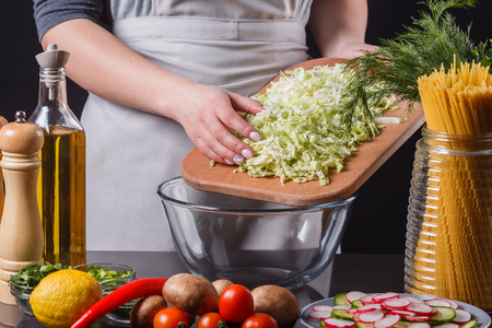 Young woman putting chopped cabbage on chopping board into glass bowl Фото со стока