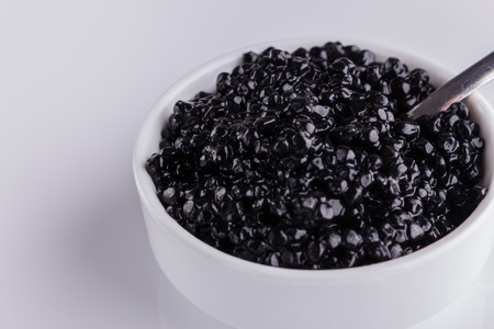 black caviar in a bowl on a white acrylic background.