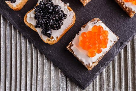 Snack with red and black caviar on a stone plate. Imagens