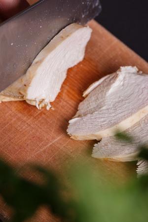 young woman in a gray apron cuts chicken breast. 版權商用圖片