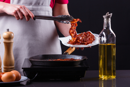 young woman in a gray apron fries bacon. Imagens