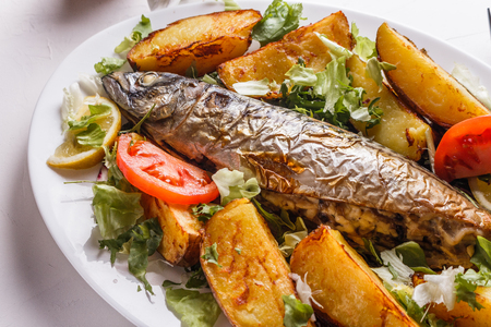 Baked stuffed fish with potatoes on the plate.