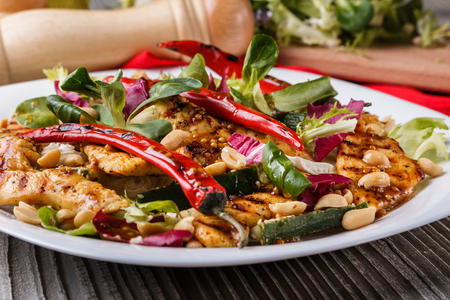 Mexican salad with hot pepper chicken fillet lettuce and nut on plate Standard-Bild - 124194107