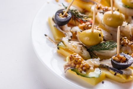 Salted herring on skewers with cheese and olives Standard-Bild - 124194115