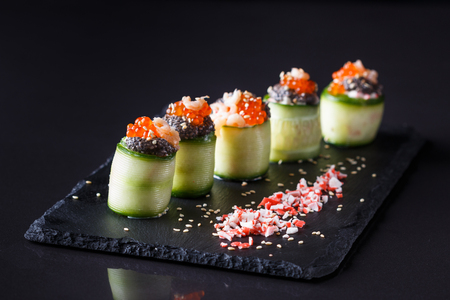rolls covered in cucumber with caviar and prawn.