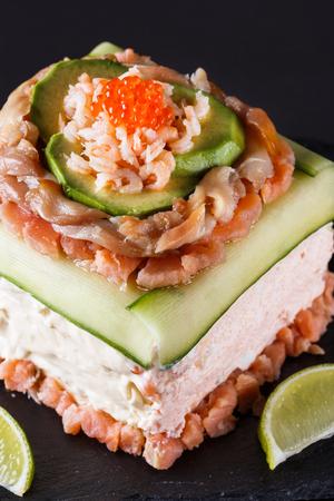 Piece of traditional savory swedish sandwich cake Smorgastorta with a caviar, mayonnaise, cucumber, square format Standard-Bild - 124194120