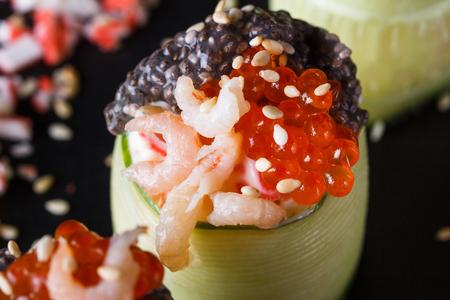 rolls covered in cucumber with caviar and prawn. Standard-Bild - 124194123