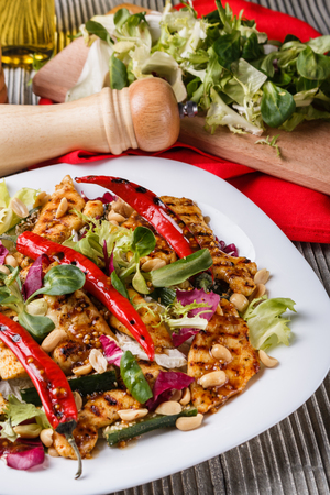 Mexican salad with hot pepper chicken fillet lettuce and nut on plate Standard-Bild - 124194128