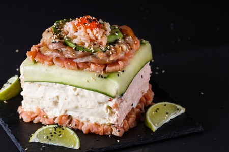 Piece of traditional savory swedish sandwich cake Smorgastorta with a caviar, mayonnaise, cucumber, square format Standard-Bild - 124194134
