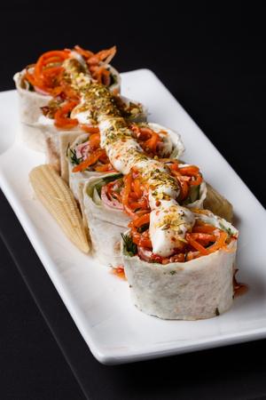 Rolls with pita stuffed carrot and ham on white plate Standard-Bild - 124194136
