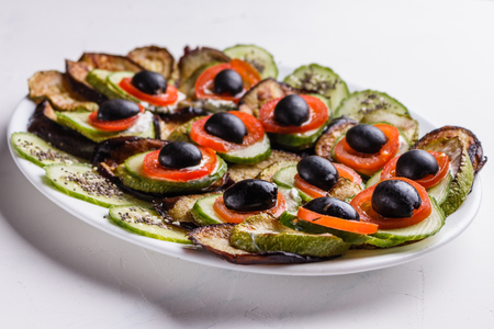 Baked eggplant and zucchini with fresh tomatoes,onions and olives. Standard-Bild - 124194137