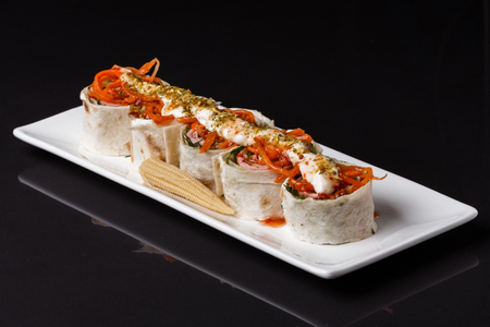 Rolls with pita stuffed carrot and ham on white plate Standard-Bild - 124194140